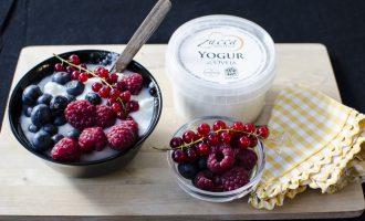 Yogur de leche de oveja en bol negro con frutos rojos y envase de yogur al lado sobre tabla de madera