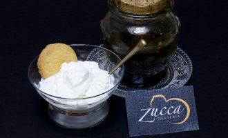 Yogur de leche de oveja en bol de cristal con galleta y tarro de miel al lado